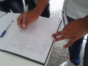 Assinaturas em apoio ao direito a voto dos imigrantes são recolhidas do lado de fora do local da votação. Crédito: Rodrigo Borges Delfim