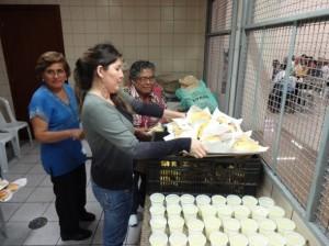 Membros da comunidade peruana servem almoço para imigrantes haitianos em São Paulo. Crédito: El Guia Latino