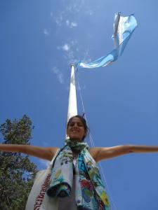 Lu Boggio em frente à bandeira da Argentina. Assim como outros imigrantes, ela tem enfrentado problemas para regularizar sua situação. Crédito: Arquivo pessoal