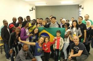 Alunos e voluntários  em projeto educacional do Adus reunidos com a bandeira do Brasil. Crédito: Divulgação