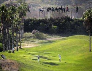 Imigrantes em cerca ao lado de campo de golfe em Melilla, enclave espanhol no Marrocos. Crédito: Jose Palazon