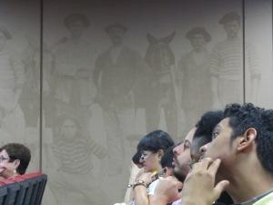 """No auditório, participantes do presente são """"espiados"""" pelos antigos acolhidos pela Hospedaria do Brás. Crédito: Rodrigo Borges Delfim"""