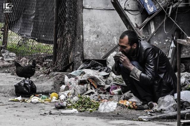 Um sírio-palestino comendo o que encontrou no lixo. Fotografia 2015/03/03 por LensDimashqi on Tumblr. Usada sob CC.BY. 2.0