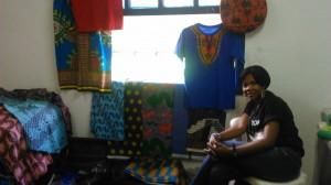 A haitiana Ali Arloude ao lado das roupas feitas típicas vendidas no evento do GRIST