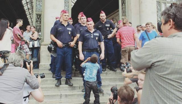 Com uma gaita, garotinho para policiais em Budapeste. Crédito: Rafaela Carvalho - 04.09.15